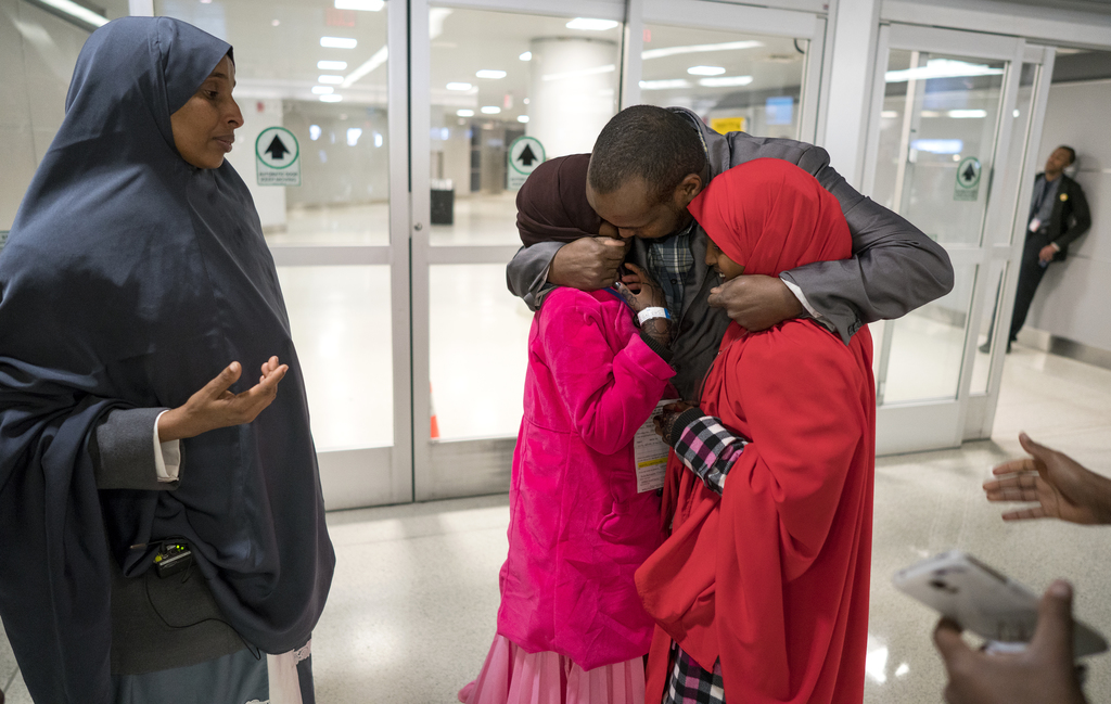 Ismail Issack, father of Miski Shalle, 11, and Muzamil Shalle, 14, embraces his children as their mother Halima Mohamed, far left, look...