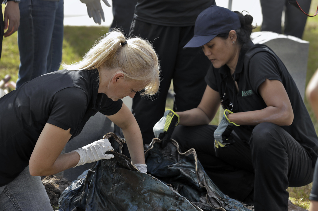 In this Sept. 15, 2016 photo, Dr. Erin Kimmerle, left, examines the remains of a 1985 female murder victim after the body was exhumed f...