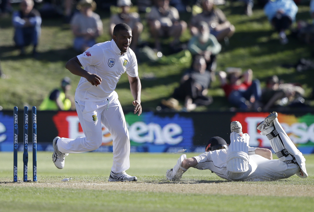 South Africa's Vernon Philander reacts after taking the bails off as he attempts to run out New Zealand's Kane Williamson, right, durin...