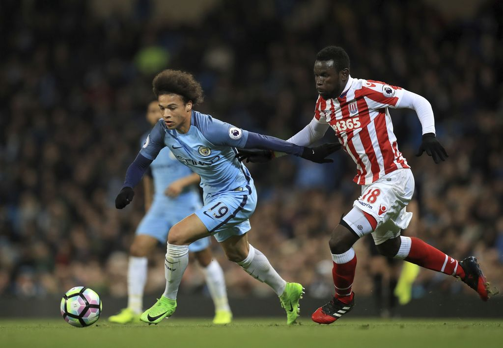 Manchester City's Leroy Sane, left, and Stoke City's Mame Biram Diouf battle for the ball during their English Premier League soccer ma...