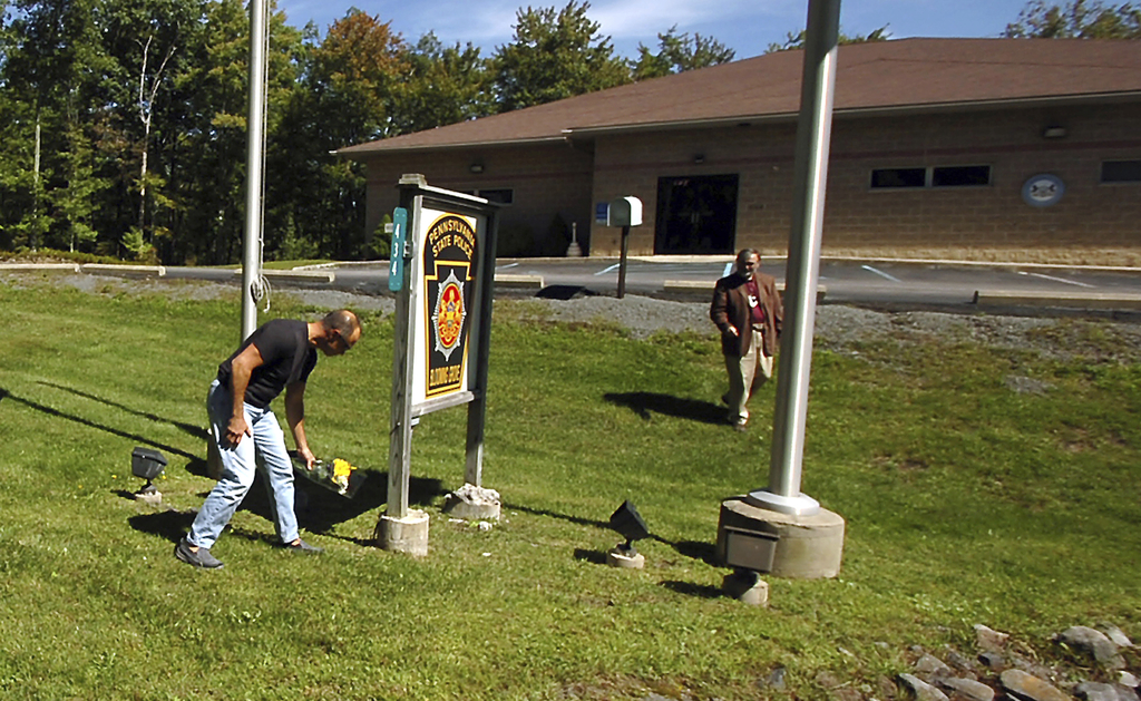 FILE - In this Sept. 14, 2014, file photo, a man places flowers in front of the Pennsylvania State Police barracks in Blooming Grove To...
