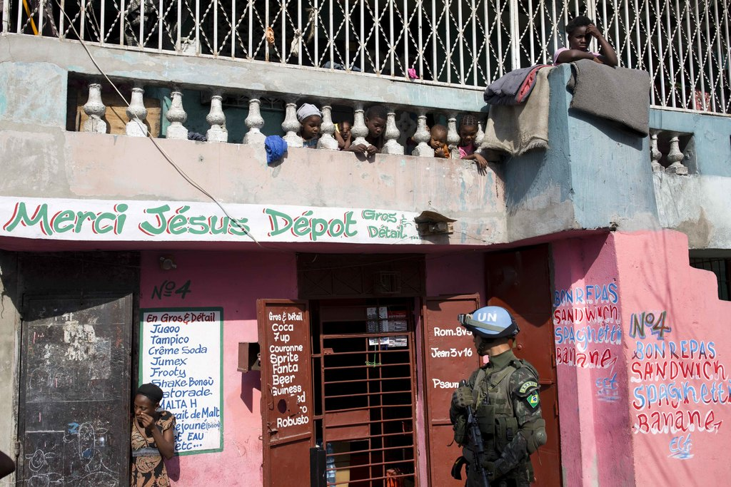 In this Feb. 22, 2017 photo, children watch from a balcony as a U.N. peacekeeper from Brazil patrols in the Cite Soleil slum, in Port-a...