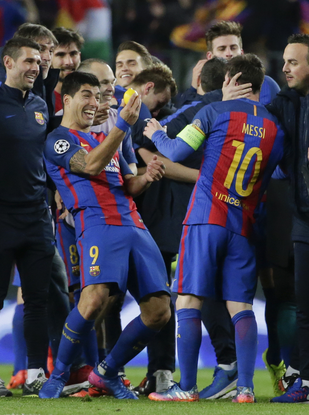 Barcelona's Luis Suarez, left, holds a lemon as he celebrates with his teammate Lionel Messi at the end of the Champions League round o...