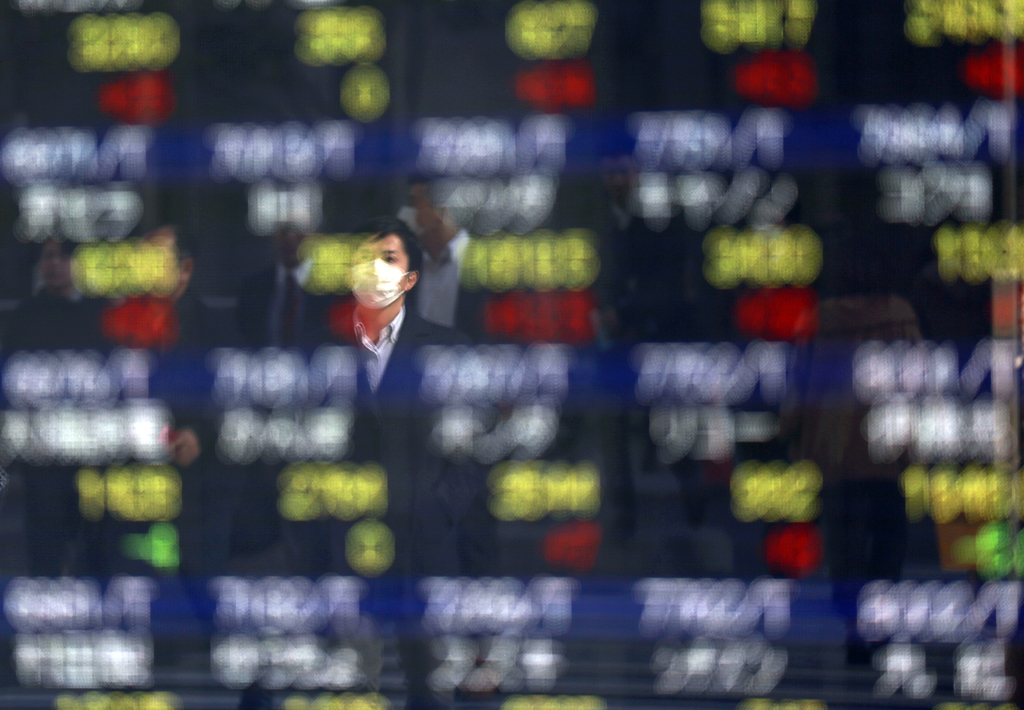 A man is reflected on an electronic stock board of a securities firm in Tokyo, Thursday, March 9, 2017. Asian stock markets were mostly...