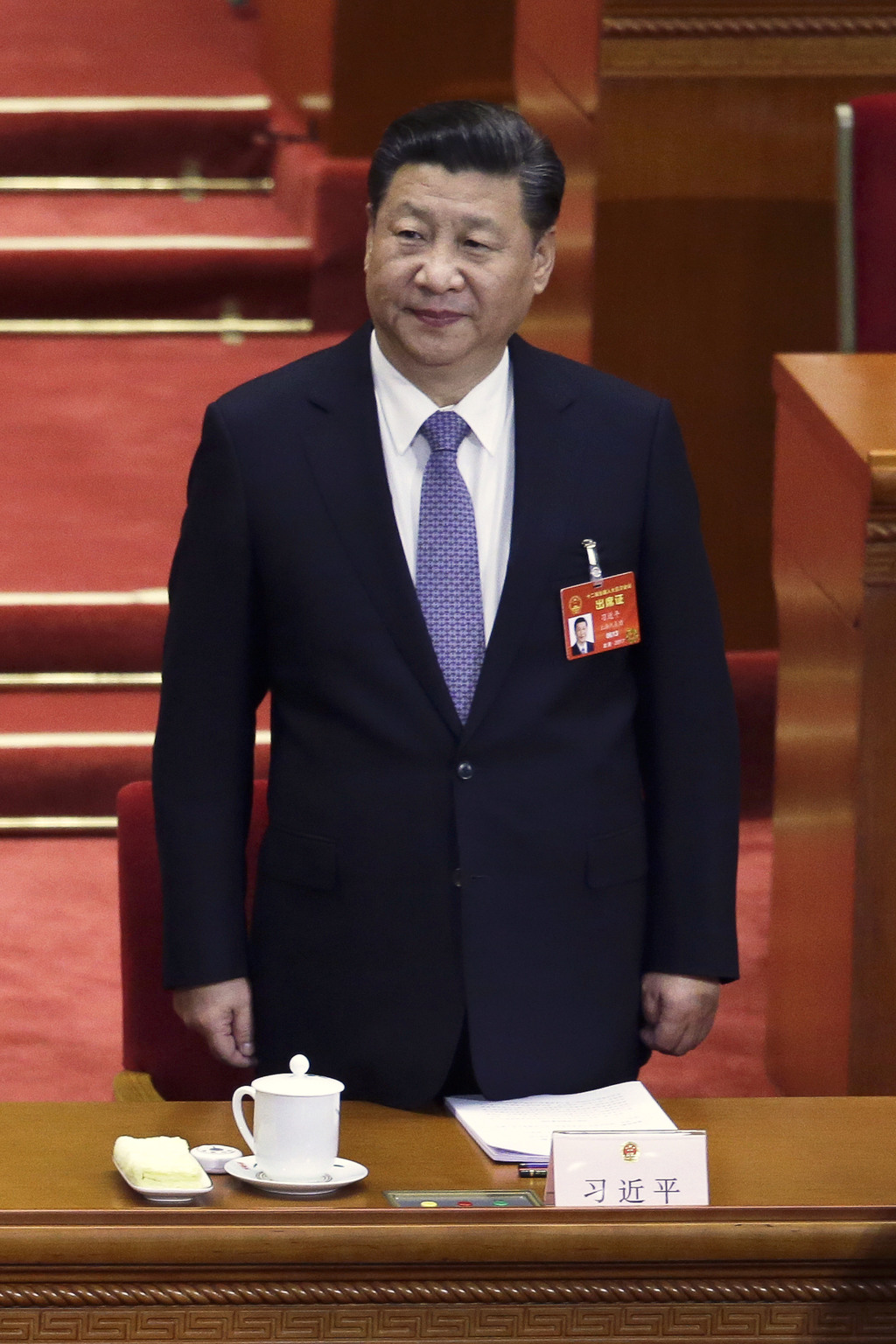 In this Wednesday, March 8, 2017 photo, Chinese President Xi Jinping stands during a plenary session of China's National People's Congr...