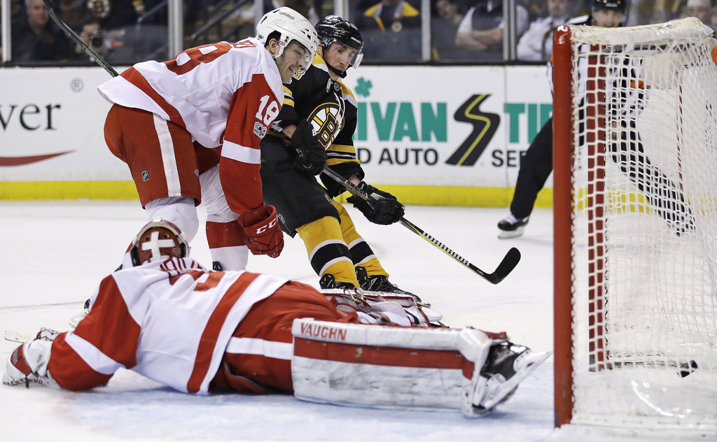 Boston Bruins left wing Brad Marchand, center, finds an opening for a goal behind Detroit Red Wings goalie Petr Mrazek (34) during the ...