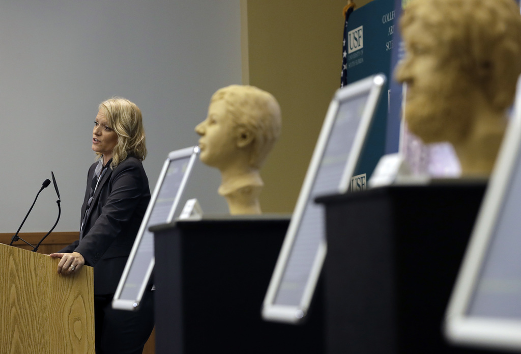 In this Oct. 21, 2016 photo, Dr. Erin Kimmerle, standing next to forensic sculptures of unidentified murder victims, speaks to a group ...