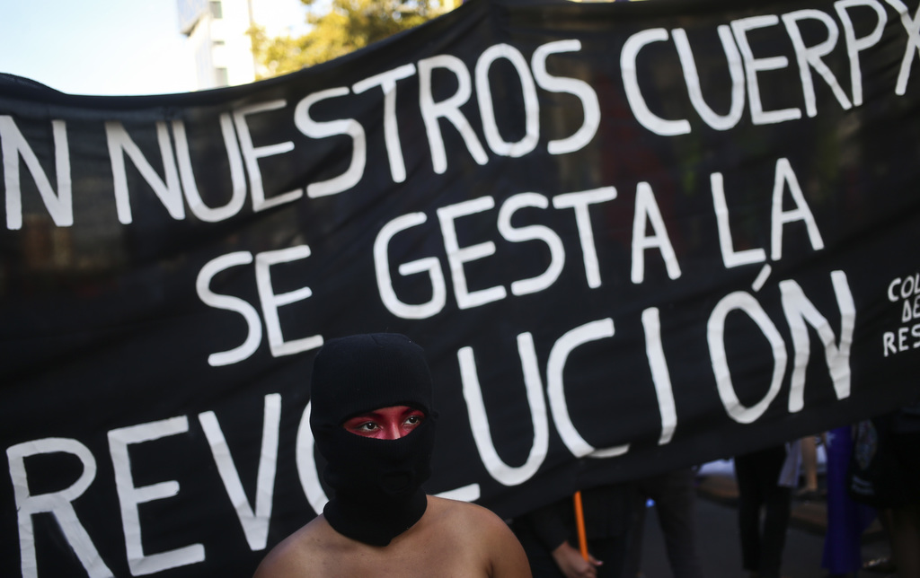 "A masked woman walks in front of a banner that says in Spanish: ""The revolution gestates in our bodies"" at a march marking Internationa..."