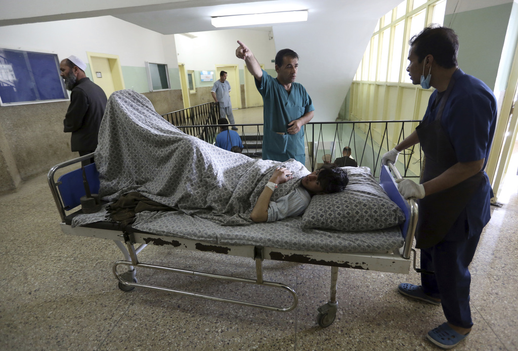 An injured man in Wednesday's attack on a military hospital is moved at a military hospital in Kabul, Afghanistan, Thursday, March 9, 2...