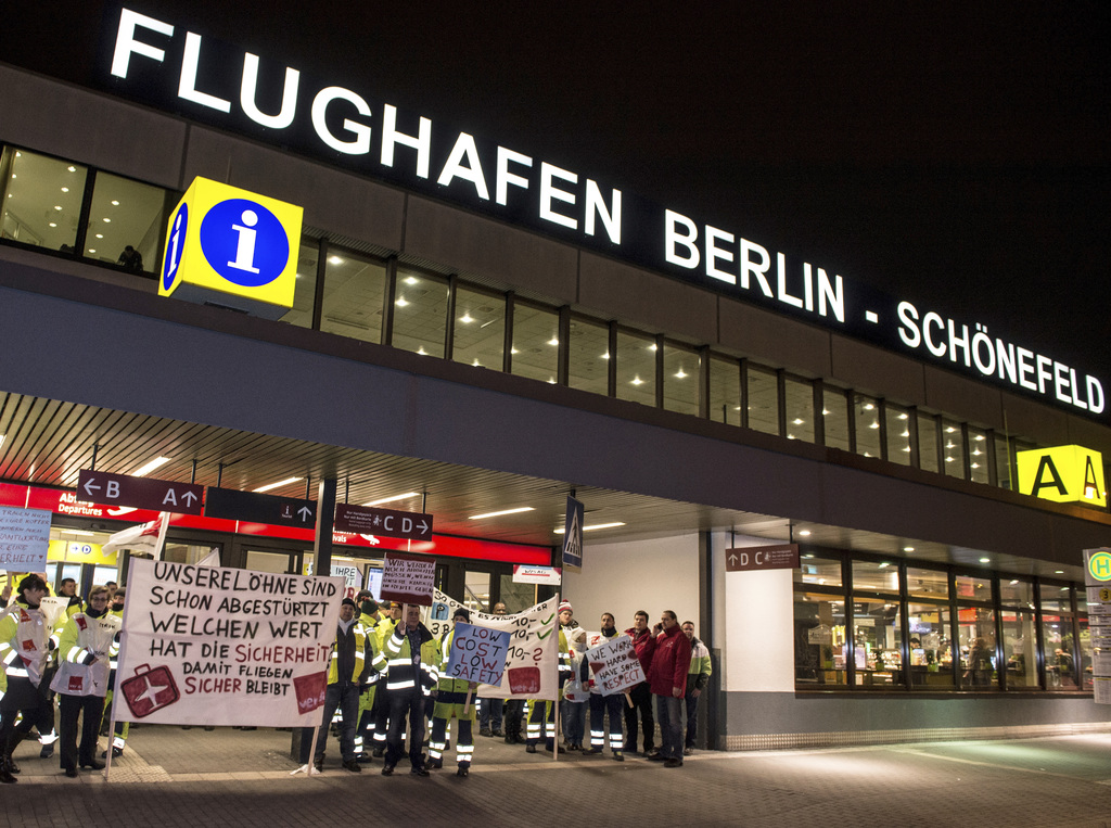 FILE - In this Feb. 8, 2017 file photo, members of the airport ground staff stand at Schoenefeld airport in Berlin, during a warning st...