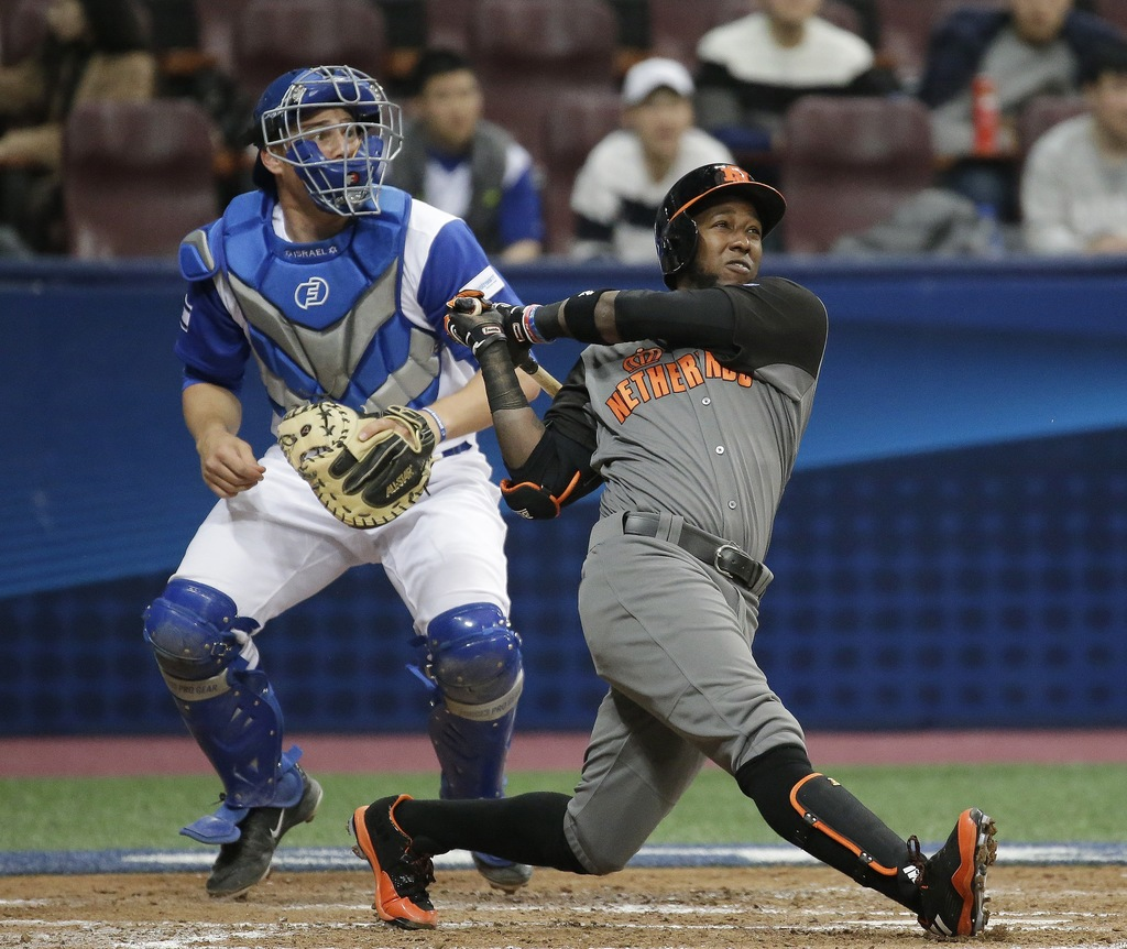 Netherlands' Jurickson Profar hits a double against Israel's pitcher Joey Wagman during the third inning of their first round game of t...