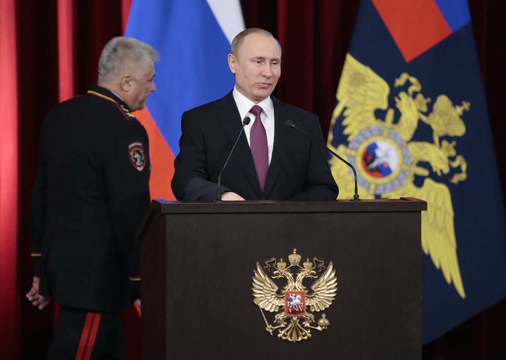 Russian President Vladimir Putin, foreground, addresses the annual meeting of Russian Interior Ministry in Moscow, Russia on Thursday, ...