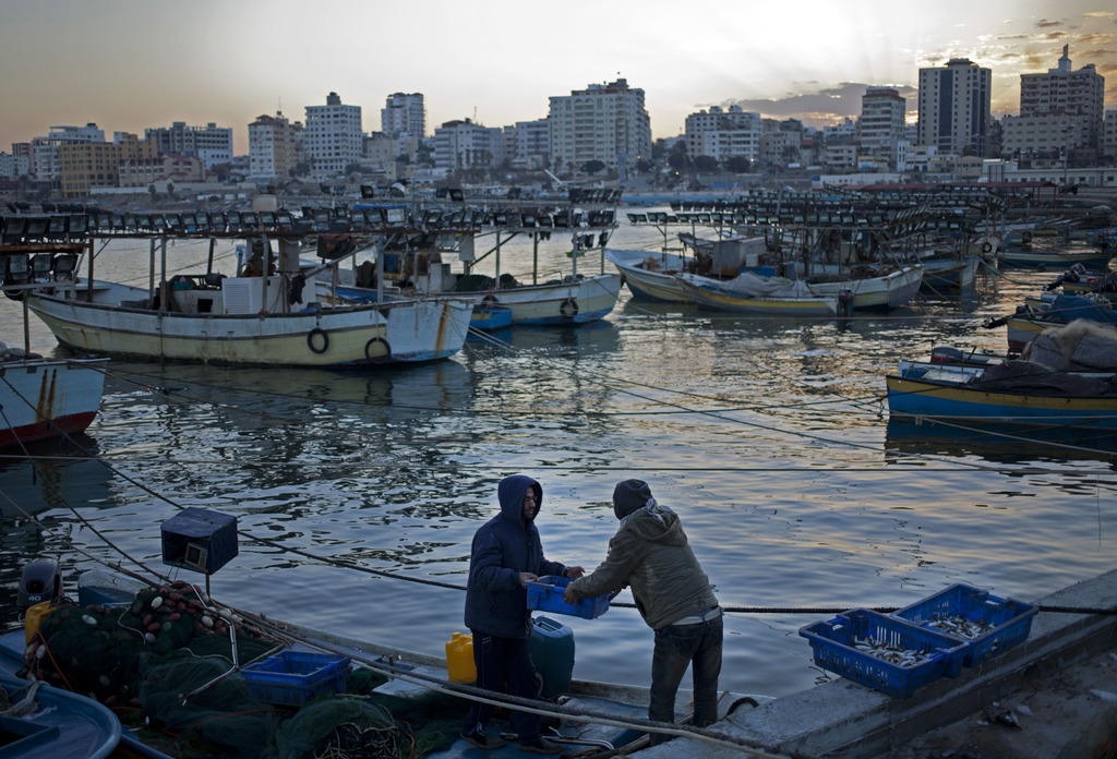 FILE -- In this Dec. 18, 2013 file photo, Palestinian fishermen unload boxes of fish from their boat in the seaport in Gaza City. Israe...