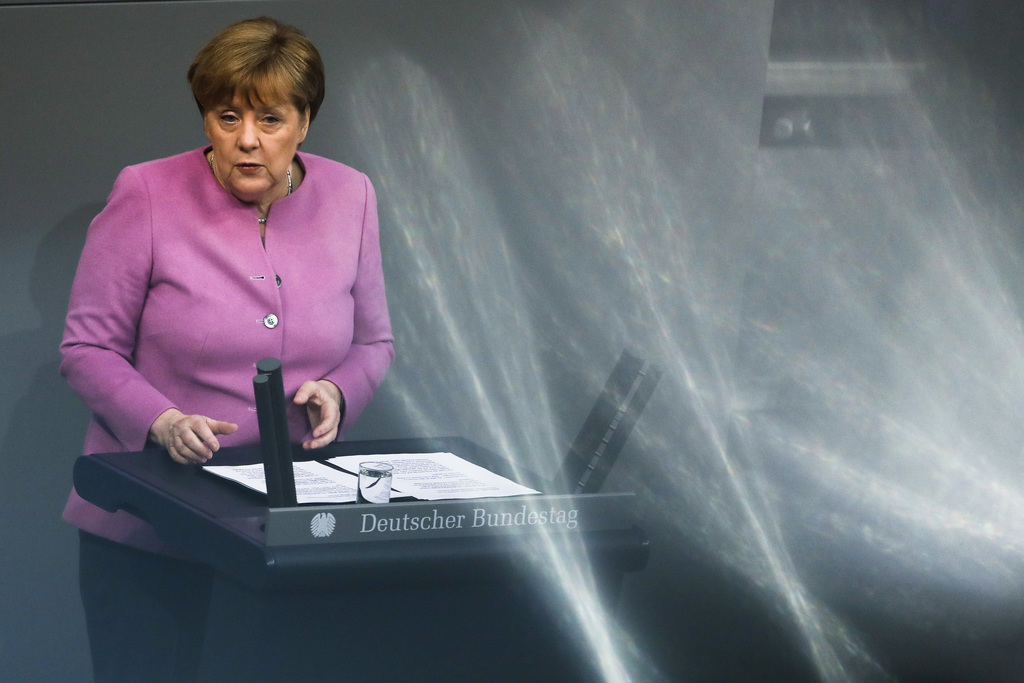 In this photo taken with reflections in windows of the visitors tribune German Chancellor Angela Merkel delivers a speech on Europe ahe...