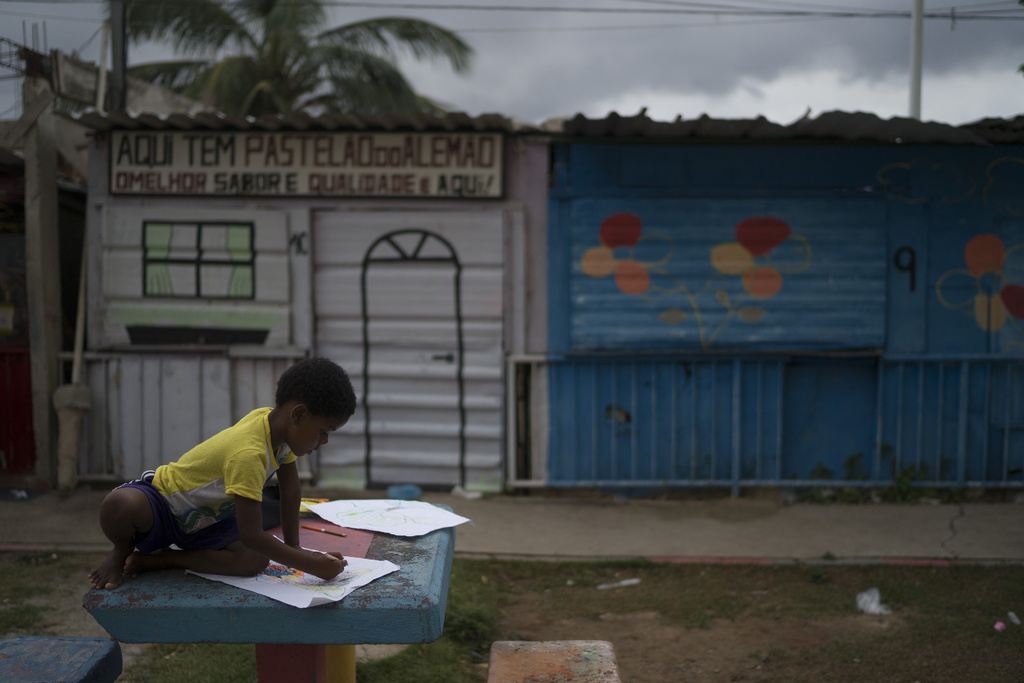 In this March 6, 2017 photo, a boy draws during a painting workshop lead by artist Mariluce Maria de Souza at the Alemao slum in Rio de...