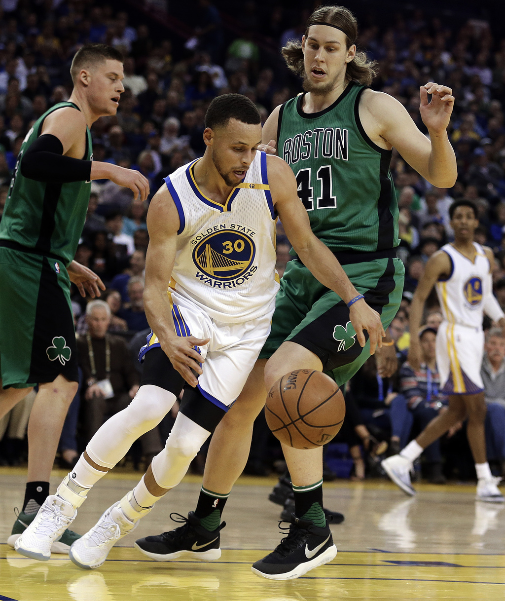 Golden State Warriors' Stephen Curry (30) drives the ball around Boston Celtics' Kelly Olynyk, right, during the first half of an NBA b...