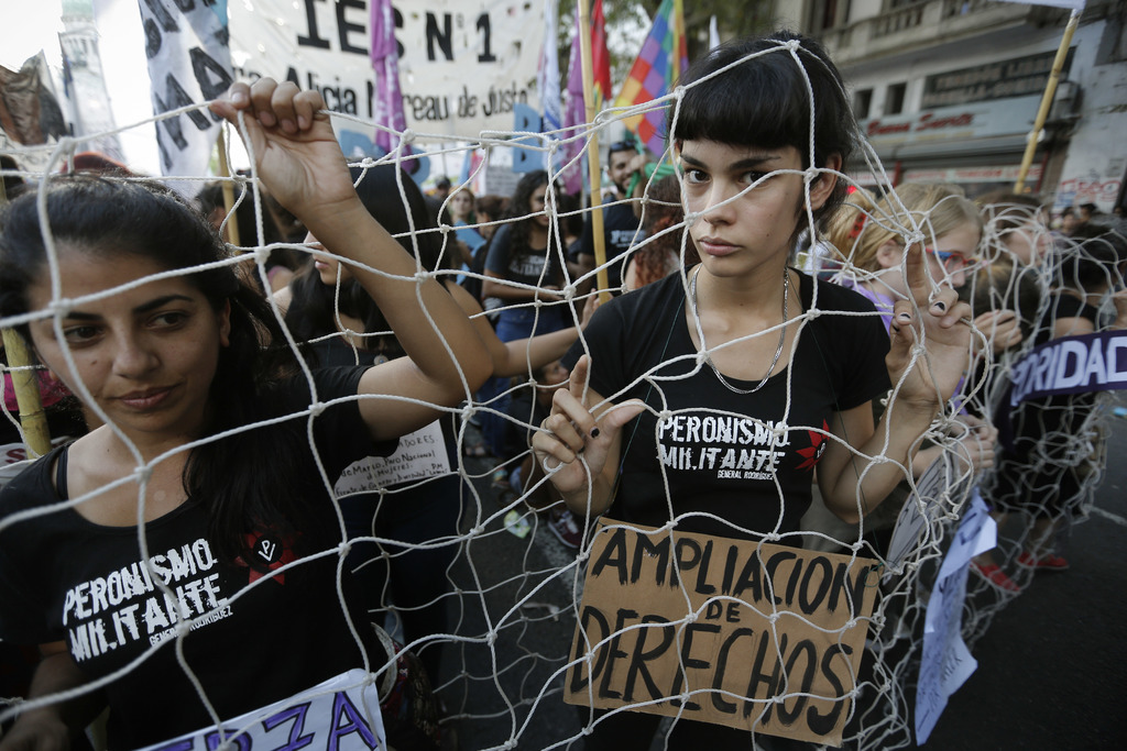 "A woman covered with a fishing net carries a sign that reads in Spanish ""More rights"" during an International Women's Day march in Buen..."