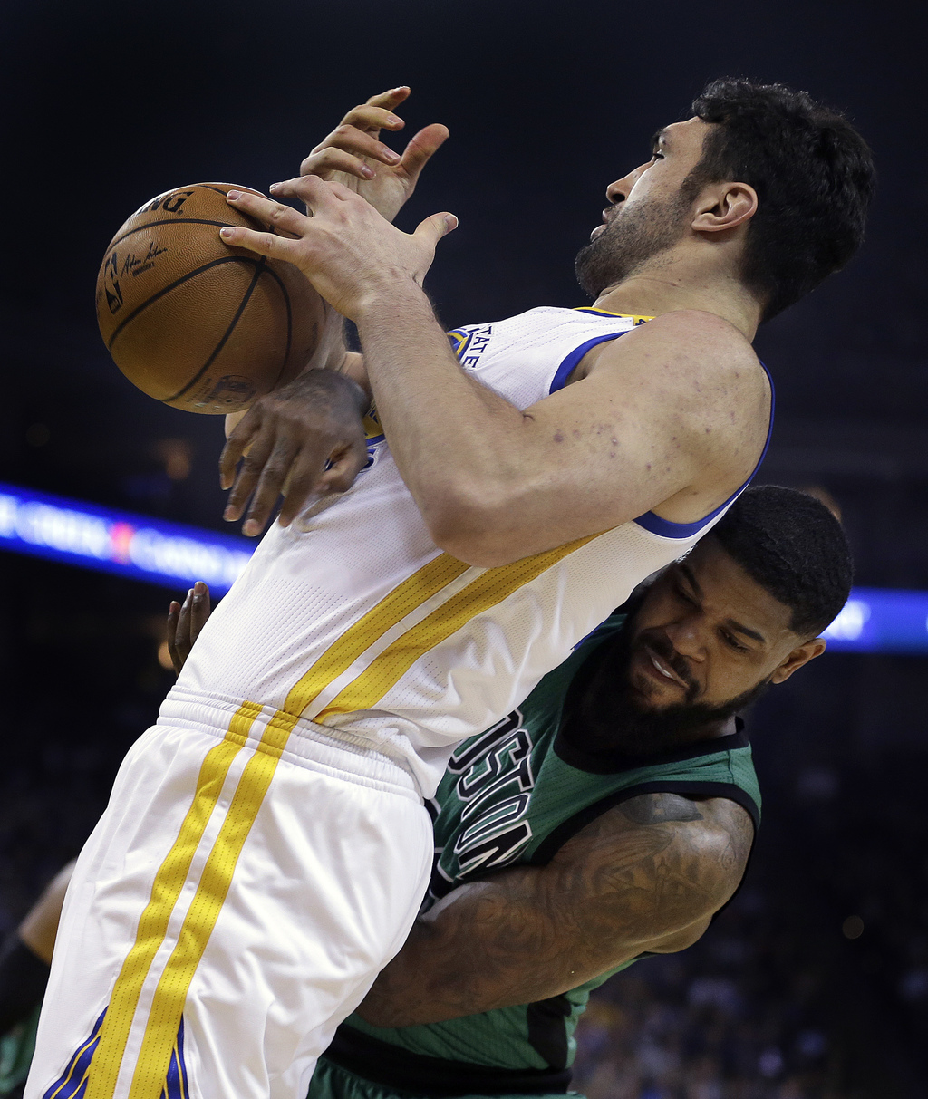 Golden State Warriors' Zaza Pachulia, left, and Boston Celtics' Amir Johnson compete for the ball during the first half of an NBA baske...