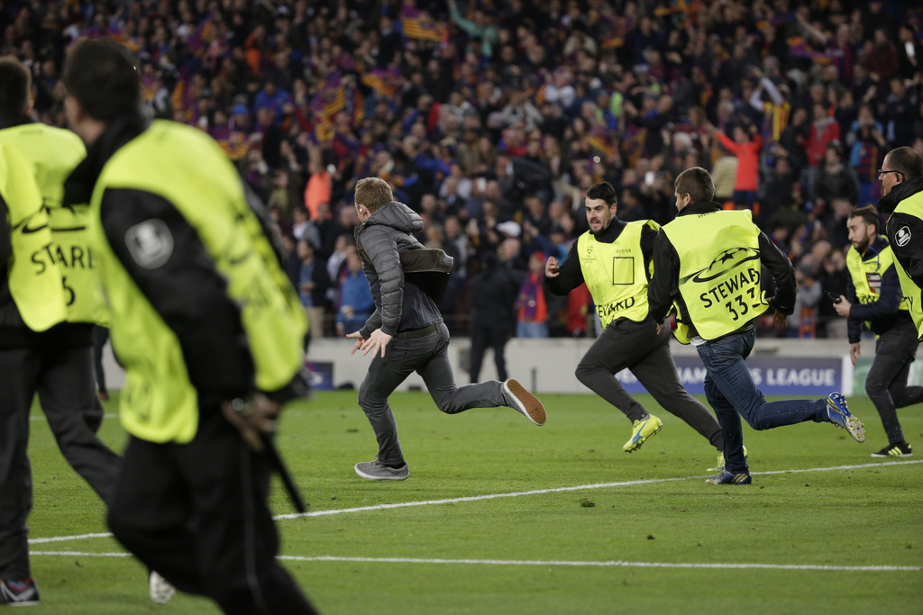 A pitch invader runs followed by stewards at the end of the Champions League round of 16, second leg soccer match between FC Barcelona ...