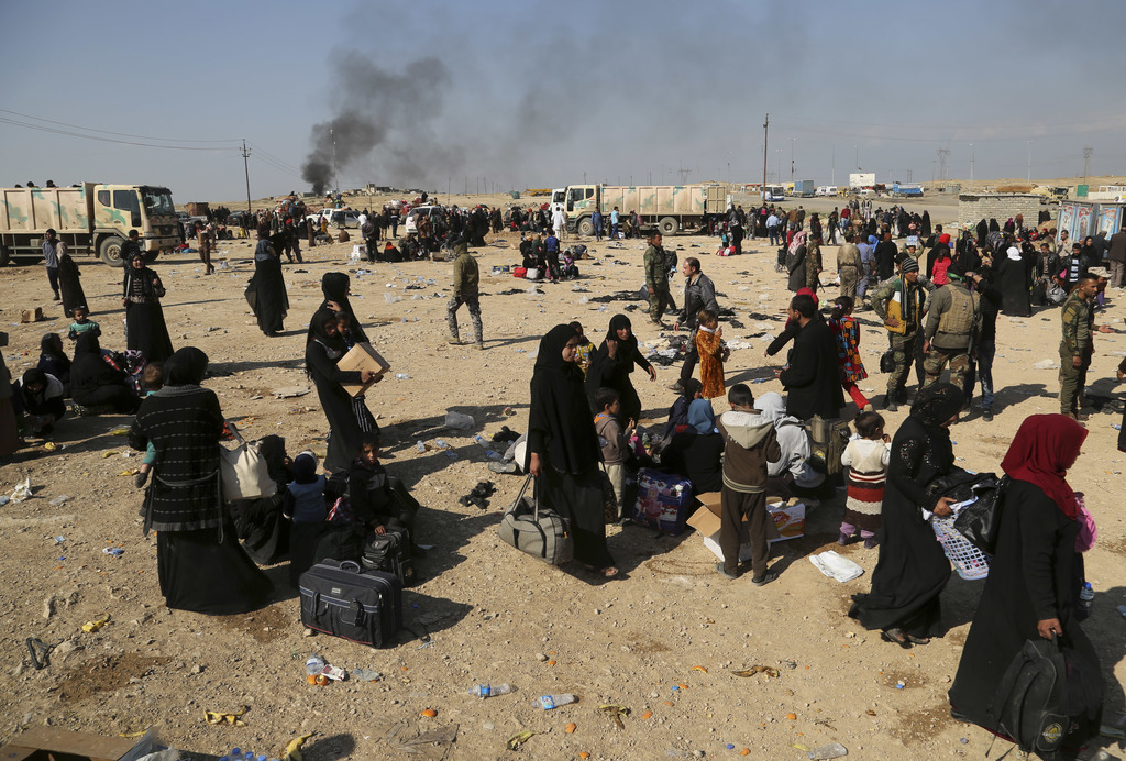 Displaced Iraqis who fled their homes due to fighting between Iraqi security forces and Islamic State militants wait to be transferred ...
