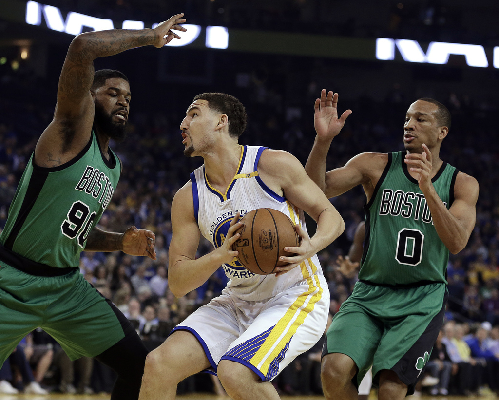 Golden State Warriors' Klay Thompson, center, looks for a shot between Boston Celtics' Amir Johnson, left, and Avery Bradley during the...