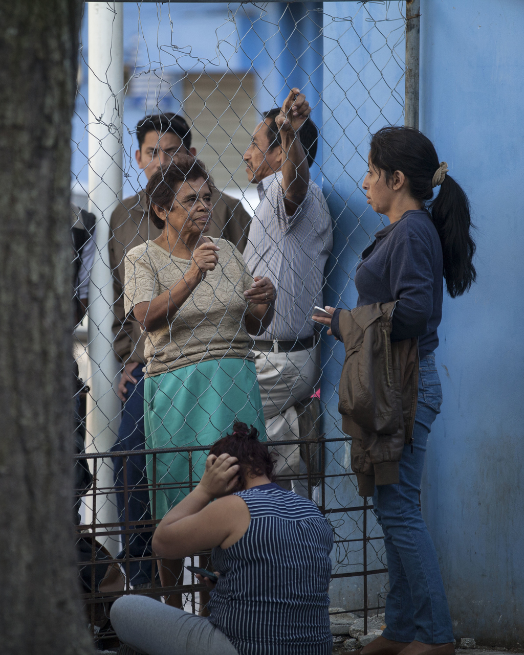 People standing outside a fence near the emergency room, left, speak with others for new information about those injured in a fire, at ...