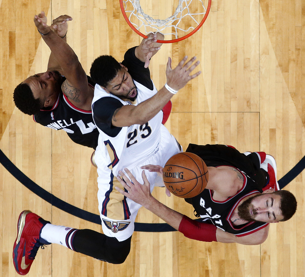 New Orleans Pelicans forward Anthony Davis (23) hits his wrist on the rim as he is fouled under the basket between Toronto Raptors guar...
