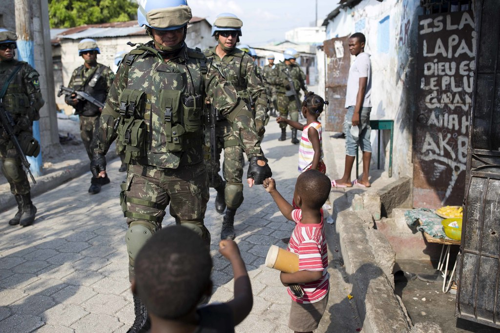 In this Feb. 22, 2017 photo, U.N. peacekeepers from Brazil fist bump with children as they patrol in the Cite Soleil slum, in Port-au-P...