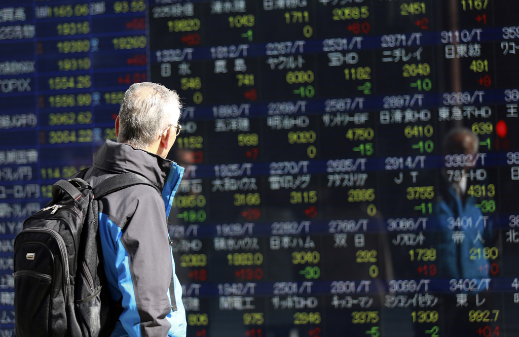 A man looks at an electronic stock board of a securities firm in Tokyo, Thursday, March 9, 2017. Asian stock markets were mostly lower ...