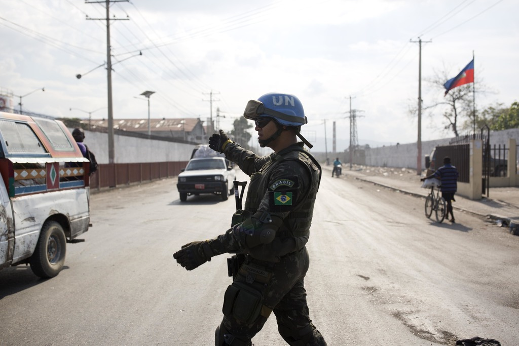 In this Feb. 22, 2017 photo, a U.N. peacekeeper from Brazil directs traffic in the Cite Soleil slum, in Port-au-Prince, Haiti. For year...