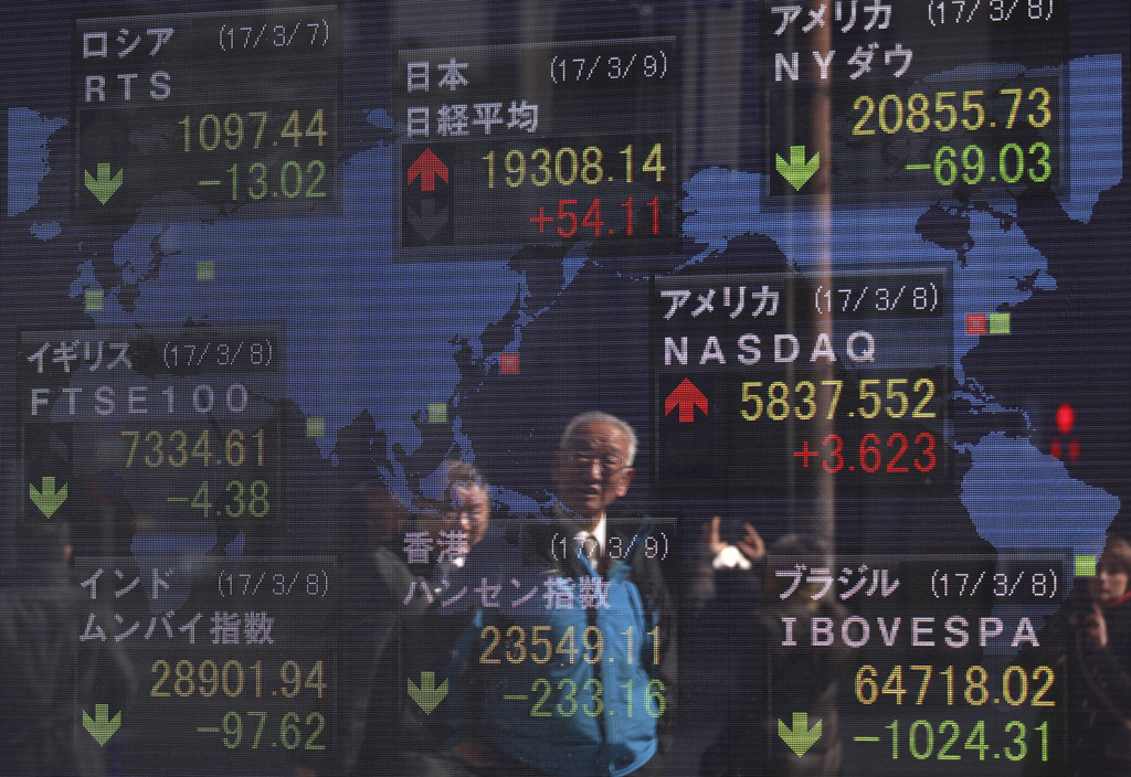 Pedestrian are reflected on an electronic stock board of a securities firm in Tokyo, Thursday, March 9, 2017. Asian stock markets were ...