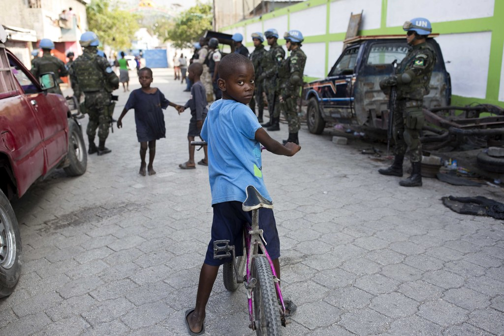 In this Feb. 22, 2017 photo, children play in the street while U.N. peacekeepers from Brazil patrol in the Cite Soleil slum, in Port-au...
