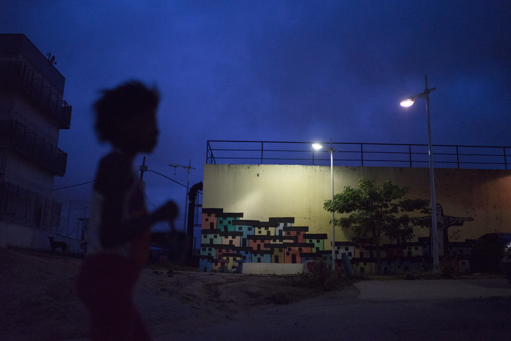 In this March 6, 2017 photo, a girl walks past a mural by Mariluce Maria de Souza, after attending Souza's painting workshop at the Ale...