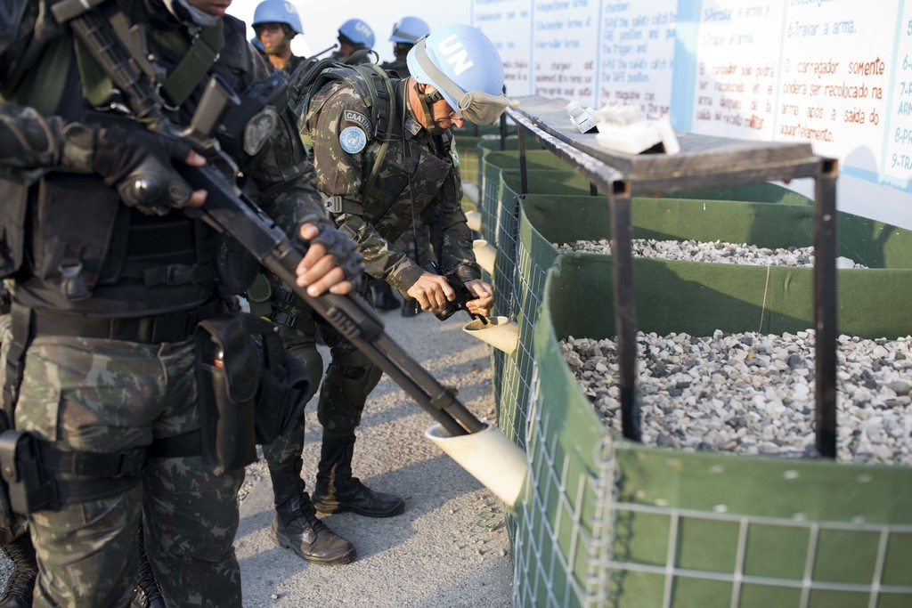 In this Feb. 22, 2017 photo, U.N. peacekeepers from Brazil discharge their guns in a weapon unloading area after patrolling in the Cite...
