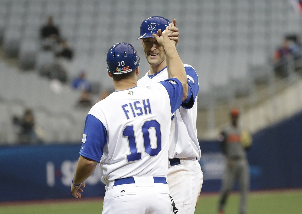 Israel's Nate Freima, right, celebrates with First Base coach Nate Fish after hitting an RBI single against Netherlands's starting pitc...