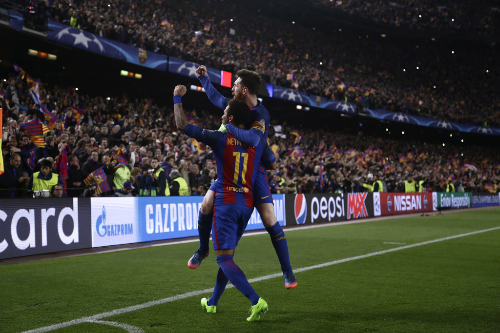 Barcelona's Lionel Messi celebrates with Neymar their victory at the end of the Champion League round of 16, second leg soccer match ag...
