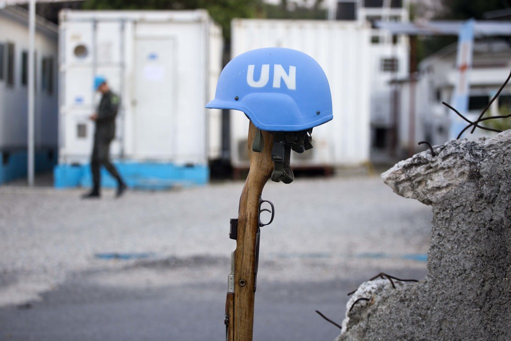 "This Feb. 22, 2017 photo shows a U.N. peacekeeper's blue helmet balanced on a weapon in Port-au-Prince, Haiti. ""We have a secure and st..."