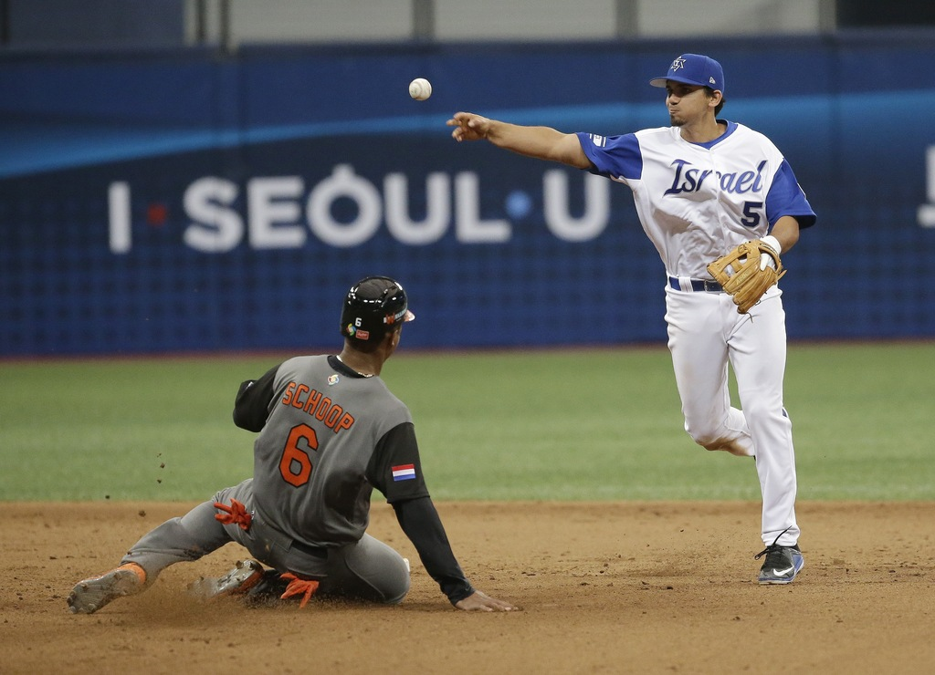 Israel's second Scott Burcham throws to first for a double play as Netherlands's Jonathan Schoop slides into second base during the 8th...