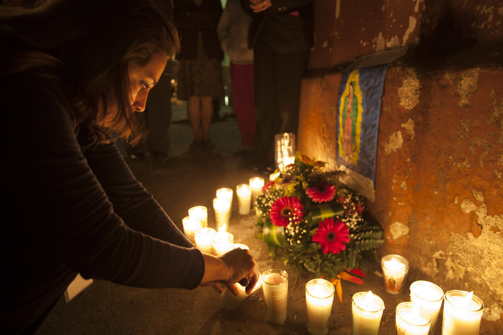 A woman lights a candle during a vigil in remembrance of the victims of a fire at a children's shelter, outside the morgue where the bo...