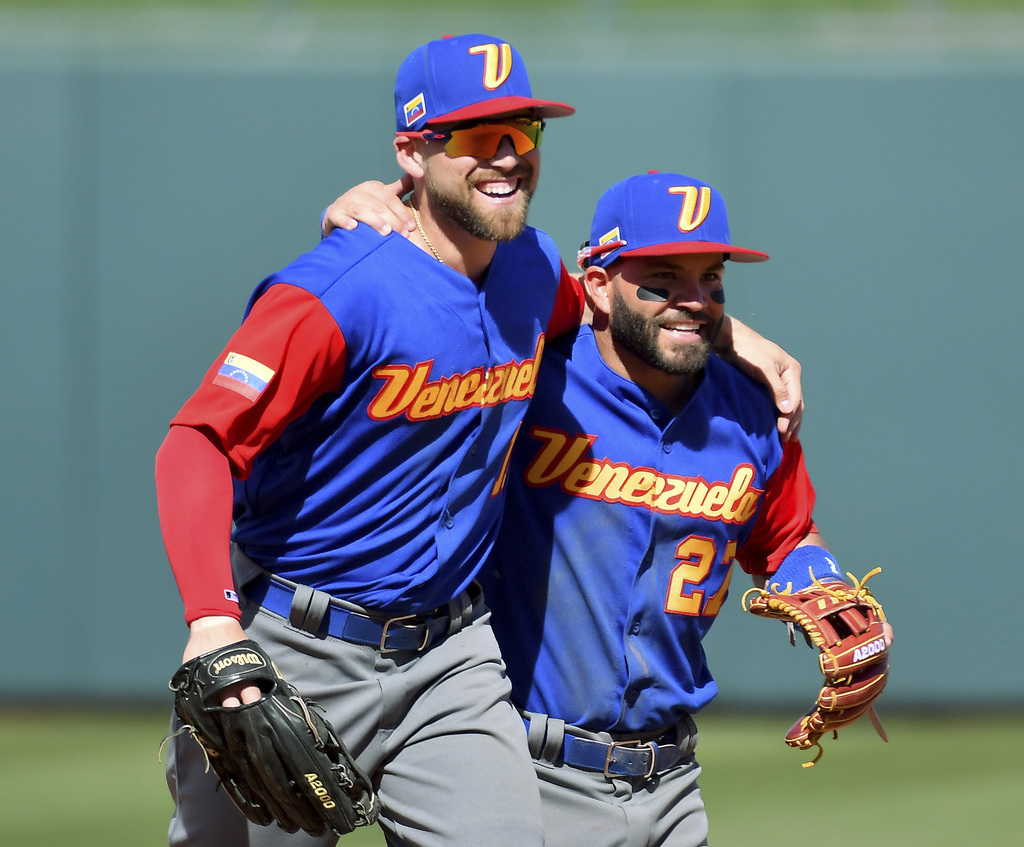 Venezuela center fielder Ender Inciarte, left, is congratulated by second baseman Jose Altuve after Inciarte made a diving catch for an...
