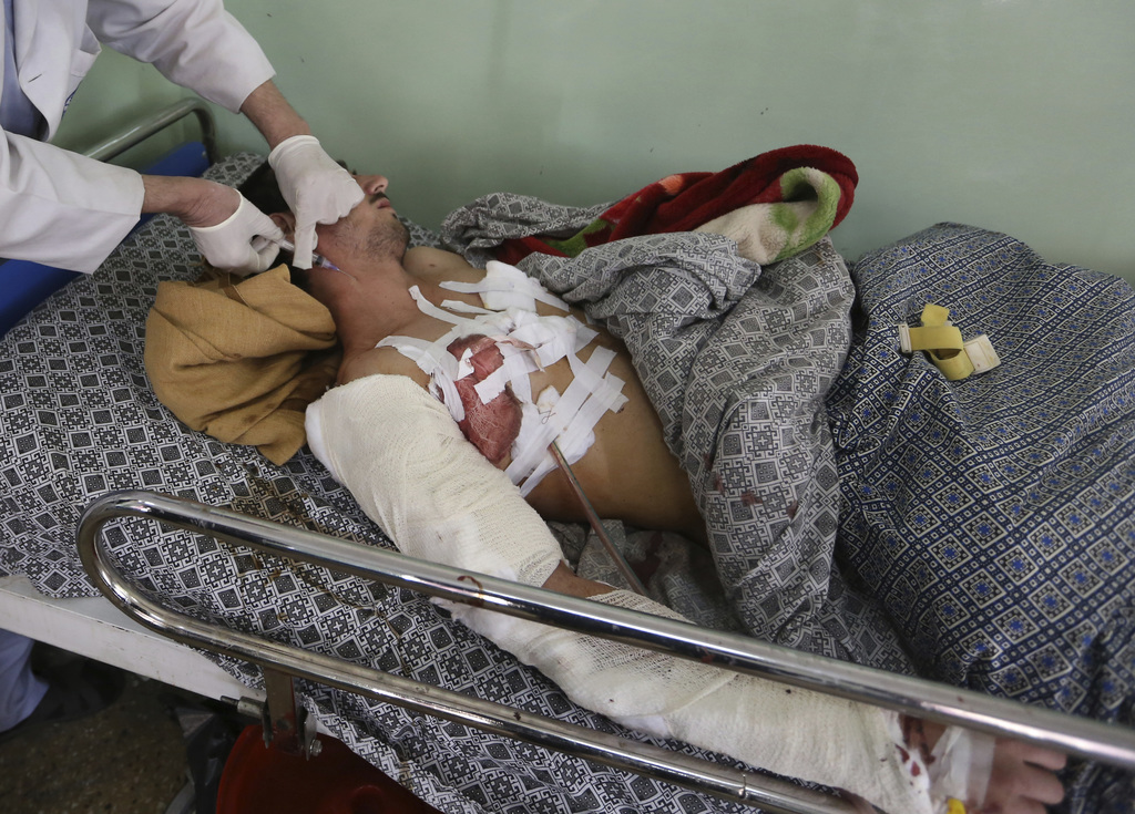 An Injured man receives treatment at a hospital after the Wednesday's attack at a military hospital in Kabul, Afghanistan, Thursday, Ma...