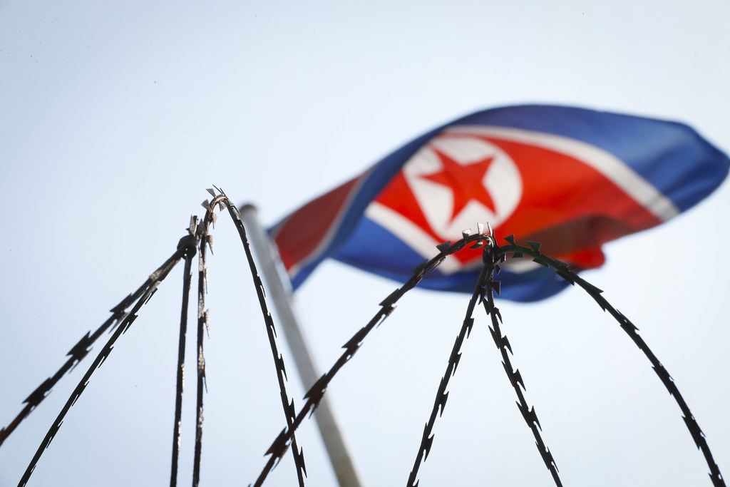 In this Thursday, March 9, 2017, photo, the North Korean flag is seen behind barbed wire on top of a wall at the North Korean Embassy i...