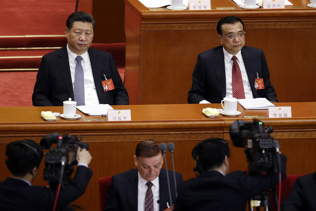In this Wednesday, March 8, 2017 photo, cameraman film Chinese President Xi Jinping, left, and Premier Li Keqiang, right, during a plen...