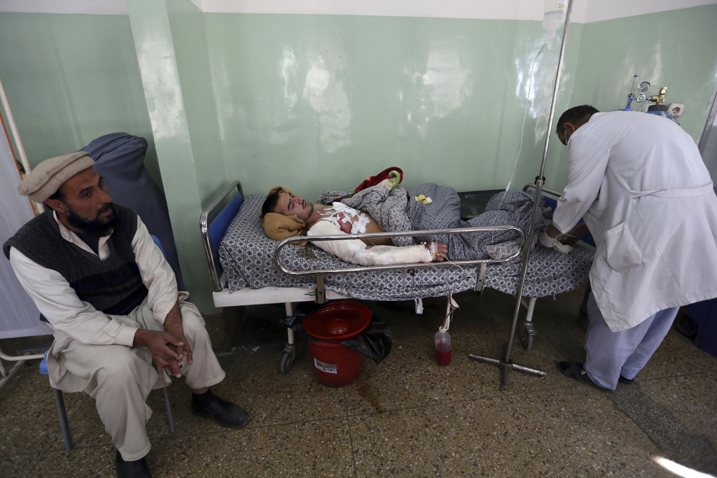 An injured man receives treatment at a hospital after the Wednesday's attack and shooting at a military hospital in Kabul, Afghanistan,...