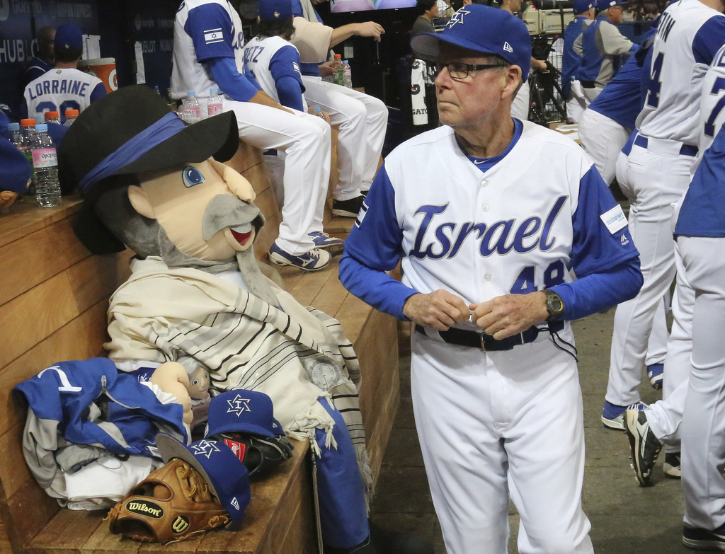 Israel's third base coach Pat Doyle, right, passes by his team mascot, The Mensch on the Bench, during at the first round game of the W...