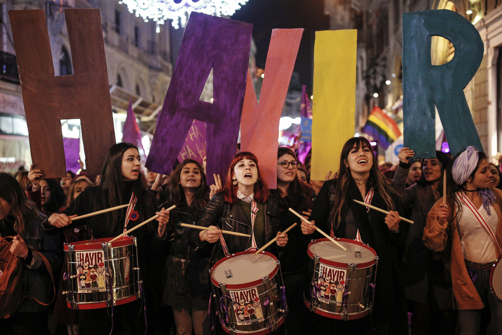 Women holding letters forming the word 'NO' in Turkish, play drums and chant slogans during a protest marking the International Women's...