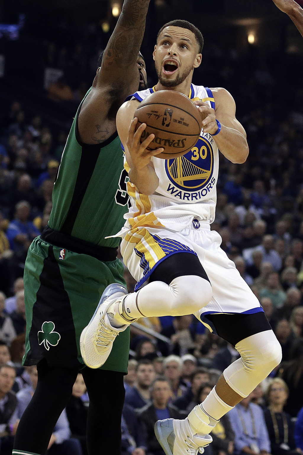 Golden State Warriors' Stephen Curry (30) lays up a shot past Boston Celtics' Amir Johnson during the first half of an NBA basketball g...
