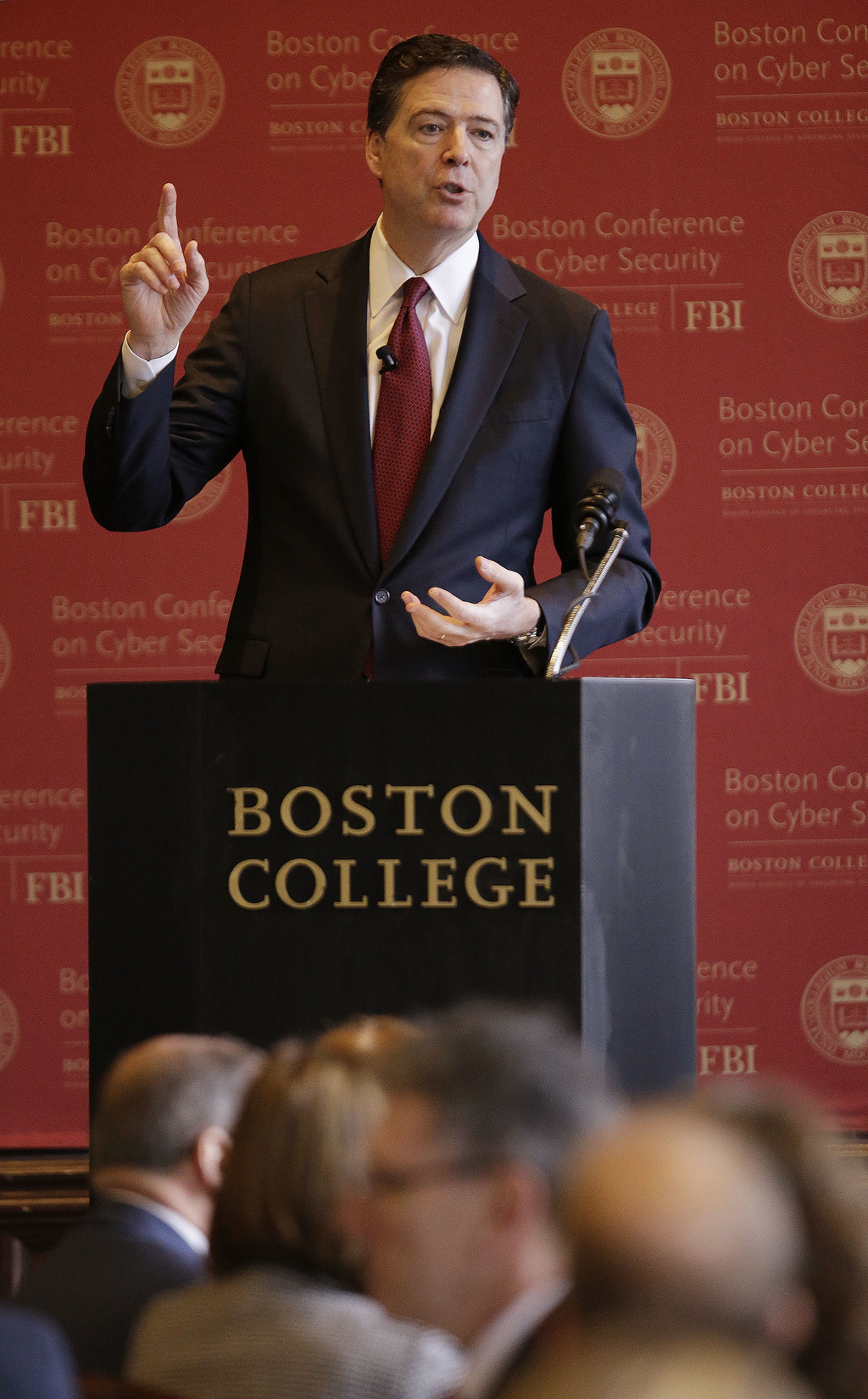 FBI Director James Comey gestures as he speaks on cyber security at the first Boston Conference of Cyber Security at Boston College, We...