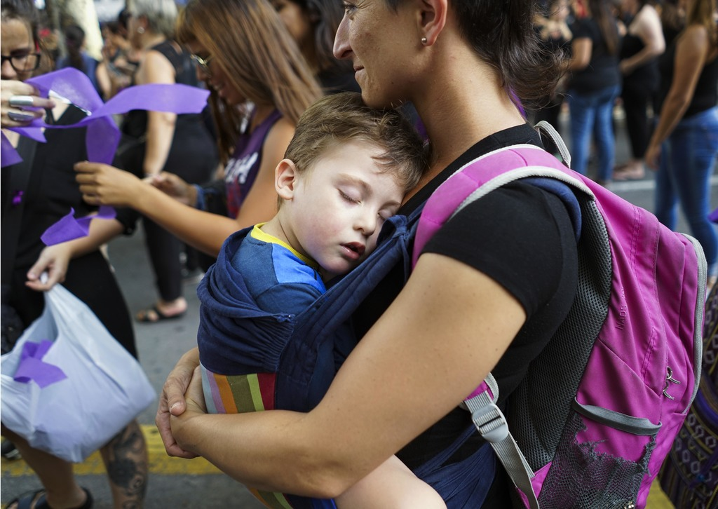A woman carries her son during a rally marking International Women's Day in Montevideo, Uruguay,Wednesday, March 8, 2017. (AP Photo/Mat...