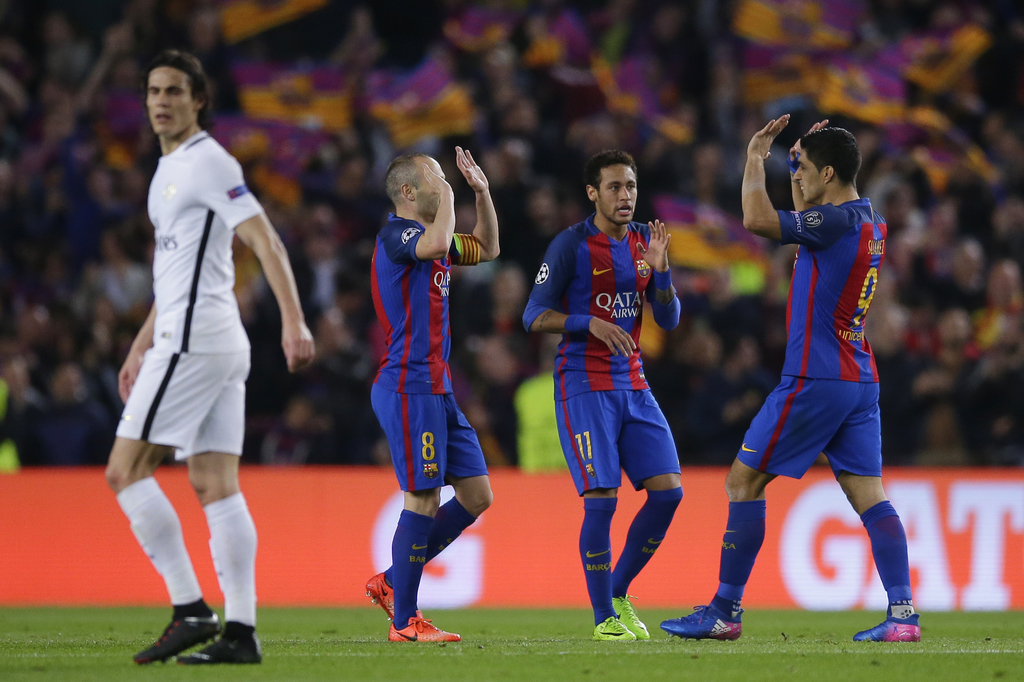 Barcelona's Andres Iniesta, 2nd left, celebrates with Neymar and Luis Suarez after PSG's Layvin Kurzawa scored an own goal during the C...